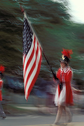 Americana Band drum major leads patriotic parade carrying american flag