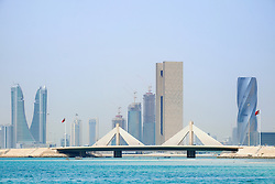 Sheikh Isa bin Salman Causeway Bridge, linking  Manama and Muharraq Island, and skyline of financial district of Manama  in Kingdom of Bahrain