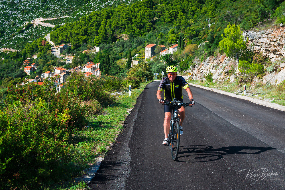 Cyclist riding through the hillside village of Maranovici, Mljet Island, Dalmatian Coast, Croatia