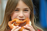young girl eating brezel bread