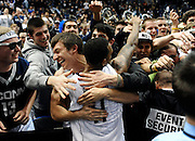 Connecticut's Ryan Boatright celebrates with students after an NCAA college basketball game win against Syracuse in Hartford, Conn., Wednesday, Feb. 13, 2013. Connecticut won 66-58. (AP Photo/Jessica Hill)
