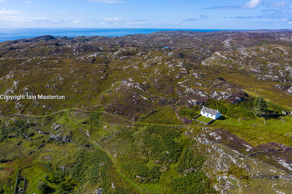 Solitary white cottage in wild landscape of Assynt near Clachtoll, north west Highlands, Scotland, Uk