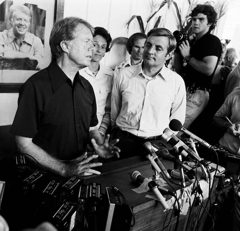 """1976 Democratic presidential nominee Jimmy Carter and his running mate Walter """"Fritz"""" Mondale with wife Joan, speak to the press at the Plains, Georgia railway depot. - To license this image, click on the shopping cart below -"""
