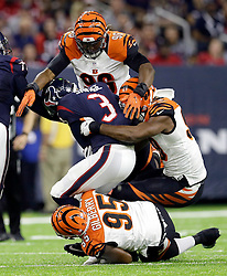 Houston Texans quarterback Tom Savage (3) is sacked by Cincinnati Bengals' Wallace Gilberry (95), Carlos Dunlap (96) and Michael Johnson, right, during the first half of an NFL football game Saturday, Dec. 24, 2016, in Houston. (AP Photo/Sam Craft)