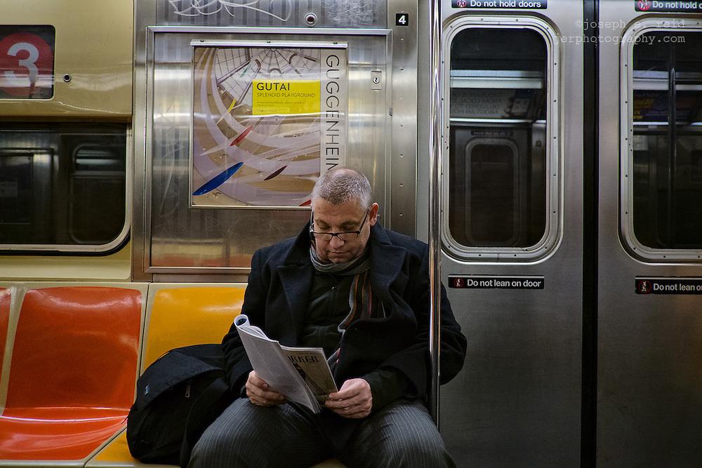 Man reading magazine on subway, New York, NY, US