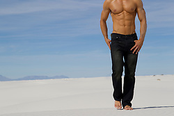 detail of a shirtless man in blue jeans standing on White Sand in New Mexico