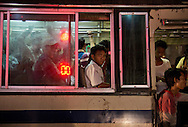 Man looks out the commuter bus in downtown Yangon, Myanmar on December 14, 2015. (Photo by Kuni Takahashi)