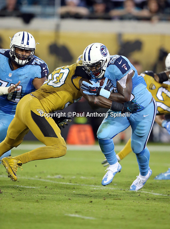 Tennessee Titans running back Antonio Andrews (26) gets tackled by Jacksonville Jaguars outside linebacker Telvin Smith (50) as he runs the ball during the 2015 week 11 regular season NFL football game against the Jacksonville Jaguars on Thursday, Nov. 19, 2015 in Jacksonville, Fla. The Jaguars won the game 19-13. (©Paul Anthony Spinelli)