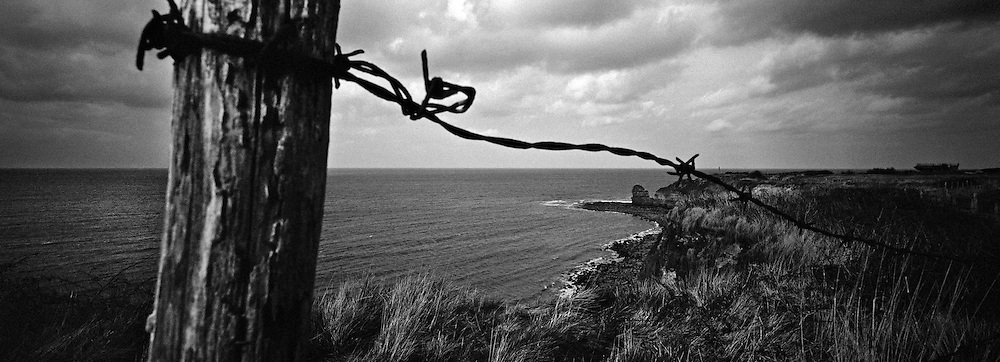POINTE-DU-HOC, FRANCE - MARCH 21: An aging barbed-wire fence lines the clifftop overlooking Pointe-du-Hoc, 21 March, 2009, Pointe-du-Hoc, France. Situated 6km west of Omaha Beach on a clifftop housing a battery of 155mm guns and the ability to fire on both Utah and Omaha, Pointe-du-Hoc was a formidable German defense to be silenced on D-Day by 225 soldiers from the US 2nd Ranger Battalion. The frontal assault required the Rangers to scale the 100ft cliff face under direct fire from the Germans above. After taking the battery with limited resistance the Rangers quickly realized the 155mm guns had not been installed and were inactive in a nearby field. More than half the Rangers, however, were killed or wounded as they fended off attacks for the next 48 hours. D-Day is regarded amongst historians as possibly the most defining day of the 20th Century, when allied forces comprising of 175,000 fighting men transported by 5,333 ships and 11,000 aircraft, landed in Nazi-occupied France and went on to liberate Europe. (Photo by Warrick Page)