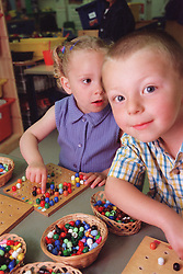 Nursery school boy and girl sitting at desk in classroom playing with wooden boards and coloured pegs,