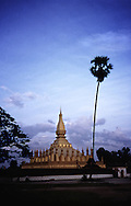Vat That Luang, Festival, Vientiane, Laos, Asia. Golden architecture of the buddhist temple at dusk with cloudy sky in background.