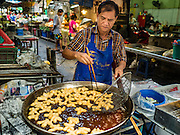 14 DECEMBER 2015 - BANGKOK, THAILAND:  A vendor fries Chinese dough sticks, which are similar to donuts, in Bang Chak Market. The market closes permanently on Dec 31, 2015. The Bang Chak Market serves the community around Sois 91-97 on Sukhumvit Road in the Bangkok suburbs. About half of the market has been torn down. Bangkok city authorities put up notices in late November that the market would be closed by January 1, 2016 and redevelopment would start shortly after that. Market vendors said condominiums are being built on the land.      PHOTO BY JACK KURTZ