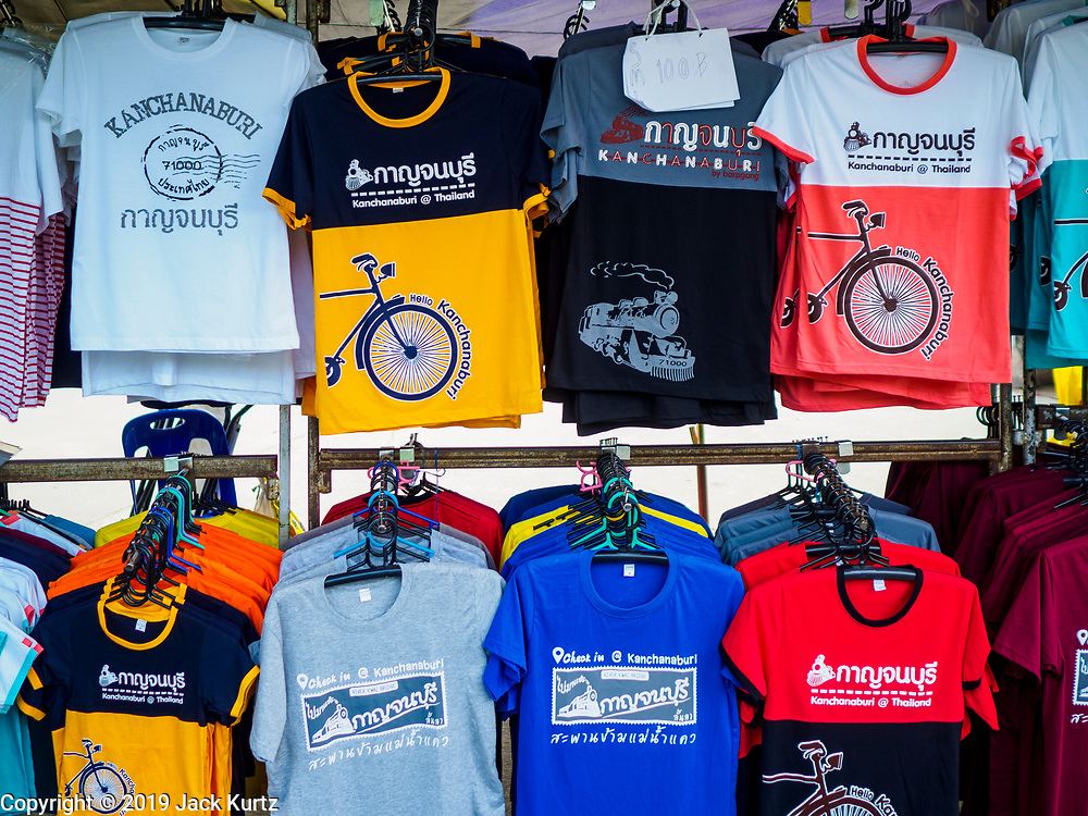 """09 JANUARY 2019 - KANCHANABURI, THAILAND: Tourist tee shirts for sale at the """"Bridge On the River Kwai"""" in Kanchanaburi. Hundreds of thousands of Asian slave laborers and Allied prisoners of war died in World War II constructing the """"Death Railway"""" between Bangkok and Rangoon (now Yangon), Burma (now Myanmar) for the Japanese during World War II.  The bridge is now one of the most famous tourist attractions in Thailand.     PHOTO BY JACK KURTZ"""