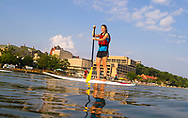 Students stand-up paddle board across Lake Mendota on a bright summer day in 2014.
