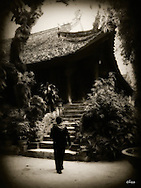Woman walks towards a staircase leading to an ancient Pagoda, Hanoi, Vietnam, Southeast Asia