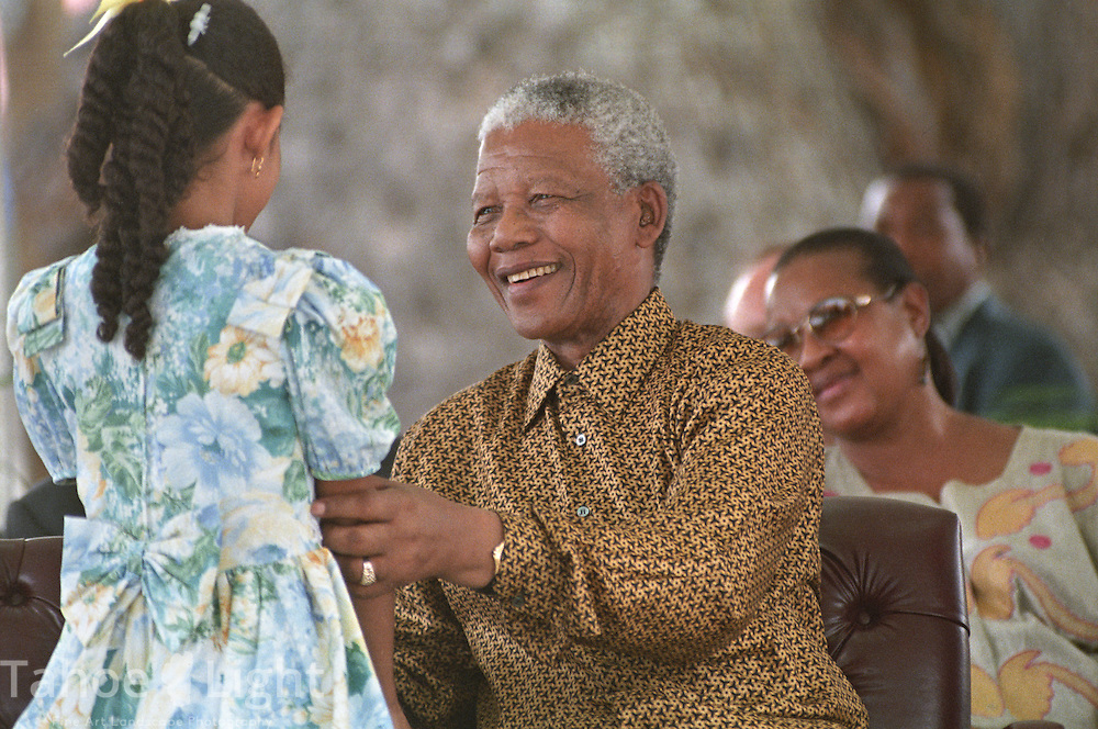 1993 Nobel Peace Prize winner Nelson Mandela greets a small child during the opening ceremonies of the Caribbean Nations economic summit on the island of St. Lucia in 1998.