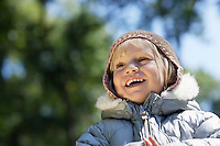 Portrait of young girl (3-4) in winter clothes laughing