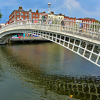 Ha'penny Bridge in Dublin, Ireland <br /> The River Liffey flows for over 80 miles before bisecting Dublin on its course to the Irish Sea.  Prior to the 19th century, a ferry was required to cross it.  When the fleet operated by William Walsh became derelict, he was told to repair them or build a pedestrian bridge. He chose the latter on condition he could charge a toll for the next 100 years. The cost to walk across the 141 feet was a ha'penny. This is how the bridge got its nickname, despite its correct name of the Wellington Bridge when it opened in 1816 and the renaming to the Liffey Bridge 20 years later. Two weeks before this photo was taken, a procession of dignitaries crossed Ha'penny Bridge to celebrate its bicentennial.