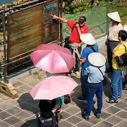A tour guide leads a group of tourists at the Imperial City in Hue, Vietnam. A self-enclosed and fortified palace, the complex includes the Purple Forbidden City, which was the inner sanctum of the imperial household, as well as temples, courtyards, gardens, and other buildings. Much of the Imperial City was damaged or destroyed during the Vietnam War. It is now designated as a UNESCO World Heritage site.