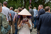 A lady wearing an Asian conical hat uses a phone to text a message during the 100th anniversary of the Royal Air Force (RAF), on 10th July 2018, in London, England. The Asian conical hat, commonly known as an Asian rice hat, coolie hat or farmer's hat, is a simple style of conical hat originating in East, South, and Southeast Asia, particularly Bangladesh, Bhutan, China, Cambodia, India, Indonesia, Japan, Korea, Laos, Malaysia, Myanmar, Nepal, Philippines, parts of Russian Manchuria and Vietnam.