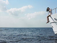 Young woman sitting at edge of yacht with legs dangling overboard side view
