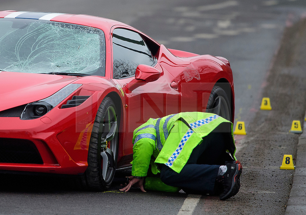 © Licensed to London News Pictures. 12/12/2016. London, UK. A member of a police investigation team examines damage to the car at the scene where six people have been rushed to hospital after a Ferrari sports car ploughed in to a group of pedestrians in Battersea, South London. Photo credit: Ben Cawthra/LNP