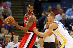 Jan 25, 2012; Oakland, CA, USA; Portland Trail Blazers power forward LaMarcus Aldridge (12) is defended by Golden State Warriors center Andris Biedrins (15) during the first quarter at Oracle Arena. Mandatory Credit: Jason O. Watson-US PRESSWIRE
