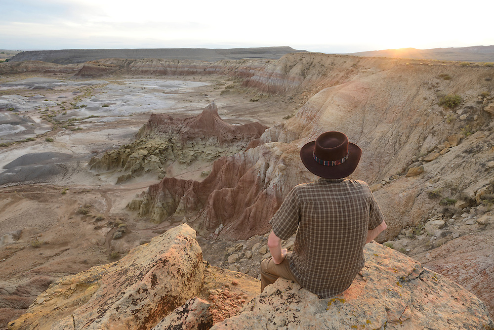 Man with hat sitting in Badlands,Devils Kitchen Badlands near Greybull,Wyoming,USA, USA<br /> Model release 0039