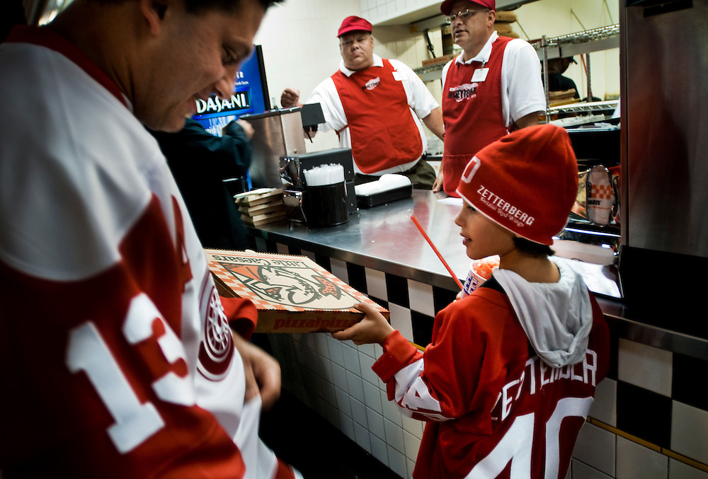 NAME NAME getting pizza with his father NAME NAME at Little Ceasar's during a Redwings game at the Joe Louis Arena in downtown Detroit..Photographer: Chris Maluszynski /MOMENT