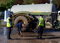 © Licensed to London News Pictures. 11/05/2012. Windsor, UK Groundmen use a suction pipe to remove mud after heavy rain. The public car parks for the show have been closed until the weekend. The Royal Windsor Horse Show in Windsor, England on May 11 2012. Photo credit : Stephen Simpson/LNP
