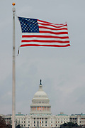 An American flag in front of the US Capitol Building on Capitol Hill. The Congress Building is divided into the Senate and the House.