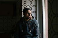 "SUTERA, ITALY - 8 JANUARY 2018: Hussain Munassar, (34), a Pakistani asylum seeker who arrived in Italy in 2015 together with his wife and that were transferred to Sutera in October 2017,  poses for a portrait in his home  in Sutera, Italy, on January 8th 2018.<br /> <br /> Sutera is an ancient town plastered onto the side of an enormous monolithic rock, topped with a convent, in the middle of the western half of Sicily, about 90 minutes by car south of the Sicilian capital Palermo<br /> Its population fell from 5,000 in 1970 to 1,500 today. In the past 3 years its population has surged  after the local mayor agreed to take in some of the thousands of migrants that have made the dangerous journey from Africa to the Sicily.<br /> <br /> ""Sutera was disappearing,"" says mayor Giuseppe Grizzanti. ""Italians, bound for Germany or England, packed up and left their homes empty. The deaths of inhabitants greatly outnumbered births. Now, thanks to the refugees, we have a chance to revive the city.""<br />  Through an Italian state-funded project called SPRAR (Protection System for Refugees and Asylum Seekers), which in turn is co-funded by the European Union's Fund for the Integration of non-EU Immigrants, Sutera was given financial and resettlement assistance that was co-ordinated by a local non-profit organization called Girasoli (Sunflowers). Girasoli organizes everything from housing and medical care to Italian lessons and psychological counselling for the new settlers.<br /> The school appears to have been the biggest beneficiary of the refugees' arrival, which was kept open thanks to the migrants.<br /> Nunzio Vittarello, the coordinator of the E.U. project working for the NGO ""I Girasoli"" says that there are 50 families in Sutera at the moment."