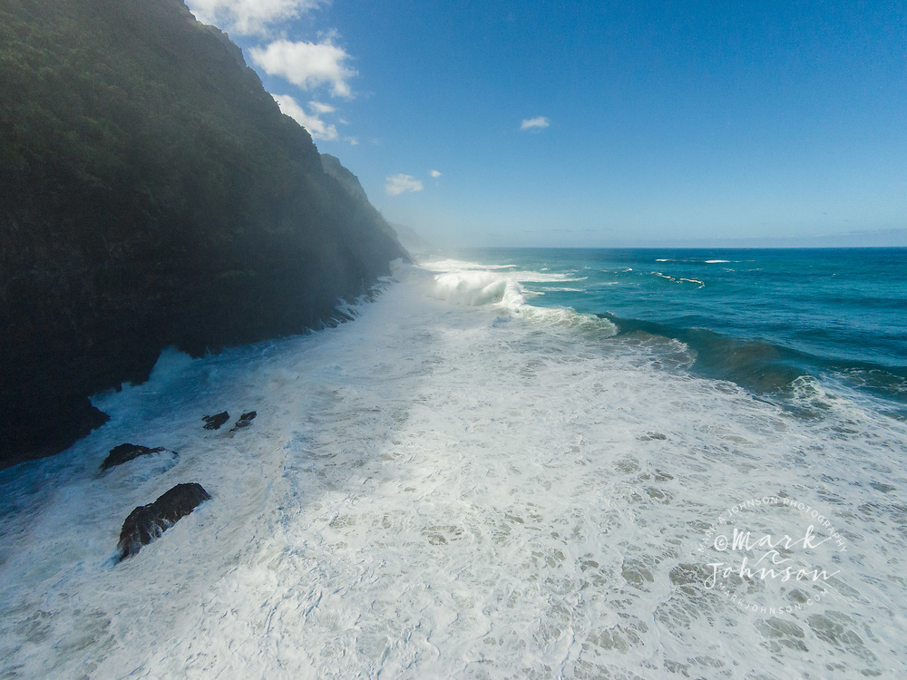 Aerial photograph of large winter storm surf hitting the cliffs of the Na Pali Coast of Kauai, Hawaii