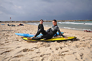 Israel, Tel Aviv two female surfers at rest on the beach
