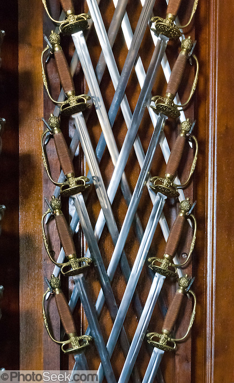 "Swords decorate the foyer of the Governor's Palace on Duke of Gloucester Street in Colonial Williamsburg, the historic district of the city of Williamsburg, Virginia, USA. Williamsburg was colonial Virginia's capital from 1699 to 1780 and a center of education and culture. The capital straddled the boundary of two of the original shires of Virginia, James City Shire (now James City County), and Charles River Shire (now York County). Here, Thomas Jefferson, Patrick Henry, James Monroe, James Madison, George Wythe, Peyton Randolph, and dozens more helped mold democracy in the Commonwealth of Virginia and the United States. Motto: ""that the future may learn from the past.""  The Historic Area exhibits colonial houses and American Revolutionary War history. Prominent buildings in Colonial Williamsburg include the Raleigh Tavern, the Capitol, The Governor's Palace, and Bruton Parish Church. Interpreters work, dress, and talk as they did in the era, teaching visitors. The 301-acre Historic Area is located immediately east of the College of William and Mary, which was founded at Middle Plantation in 1693. The new College, long a desire of the colonists, was a key factor in the establishment of the town as capital of Virginia in 1698 and its renaming for King William III of England shortly thereafter.  Jamestown and Yorktown, the other two points of the Historic Triangle, are linked to Colonial Williamsburg by the National Park Service's bucolic Colonial Parkway."
