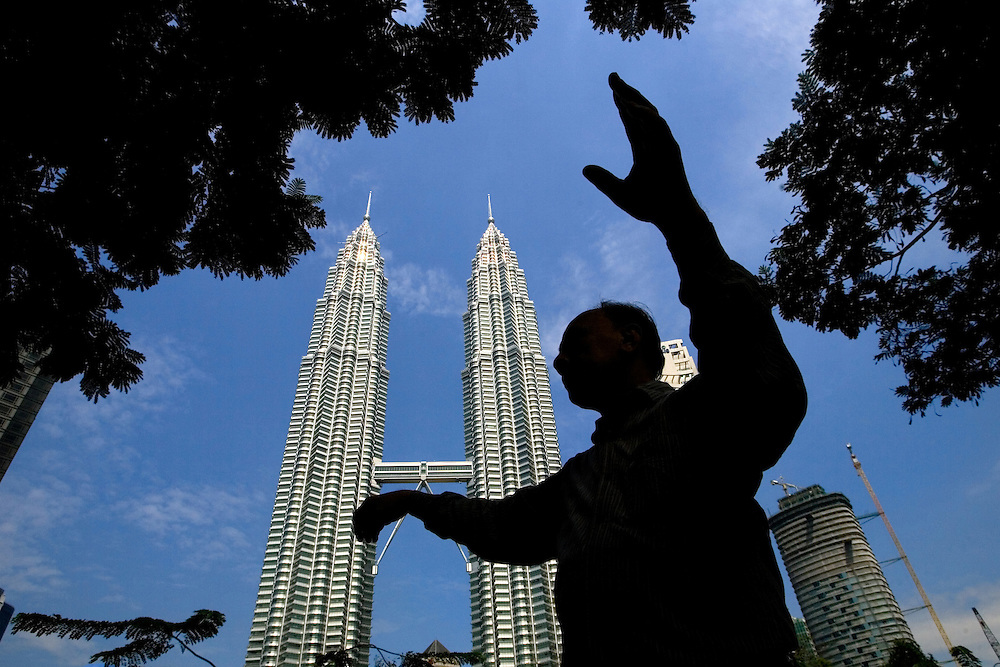 A man in silhouette practises chinese Tai Chi against Petronas Towers building. Petronas Towers (also known Petronas Twin Towers) designed by architect Cesar Pelli were completed in 1988. The 88-floor tower are still currently the world's tallest twin towers.