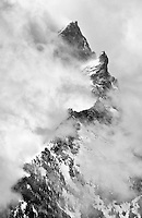 The grand teton emerges from a clearing storm covered in fresh powder