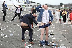 © Licensed to London News Pictures. 08/04/2016. Liverpool, UK. Two male racegoers bare all at the end of Ladies Day at the Grand National 2016 at Aintree Racecourse near Liverpool. The race, which was first run in 1839, is the most valuable jump race in Europe. Photo credit : LNP