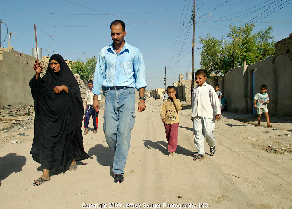 "Emad Al-Kasid, right, walks with Aoum Hussein on the way to her home in the modernized center of the village Suq ash Shuyukh on the outskirts of Nasiriyah, Iraq, Sunday, August 3, 2003. Emad was visiting the neighborhood he grew up in for the first time since 1991. ..He took an indefinate amount of time from his satellite and Arab media company in Dearborn, MI, to come home with his family. On his own, and with his own money he's been meeting with Iraqi businessmen, religious leaders and politicians trying to find ways to bring business and democracy to Iraq. ..""Can you imagine being away from you home and family for 13 years?"" he asks. ""I'm torn, do come here to stay and leave all I've built in the U.S.?""..He is hoping to teach members of his tribe, Al Hacham Al-kasid, and village that there is help available; they just have to ask for it. Another goal of this trip is to see for himself whether Iraq is safe enough for exiles to return and for foreign investment to come in...Since the 1991 uprising against Saddam Hussein in Shiite dominated Southern Iraq, people of this area have suffered greatly through his methods of disrupting daily life. For example, modernization came to a hault as money was diverted to Baath Party strongholds. Check points on on every other corner made it nearly impossible to go to work, the doctor, or visit family. Teachers made $5 U.S. per month and had to spend almost all of their salary for taxis in order to go to work...He tried to kill the people by cutting off the rivers that village survival depends on. Dams and canals dirverted the fresh water from flowing into the swamps by way of tributaries. In effect, without fresh water flowing in, the people started poisoning the water supply themselves by using it to wash and clean. Their primitive sewers still flow freely into the same waters that animals use and that feed their rice fields."