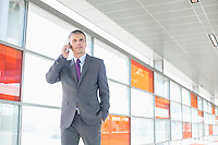 Middle aged businessman using cell phone at train station
