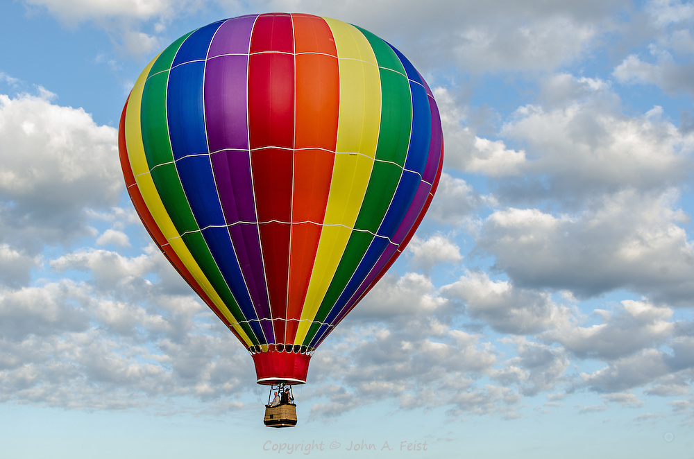 This very colorful balloon is up there in a blue sky with the clouds being nice enough to frame it.  This was a perfect day for botht he balloons and the photographers.