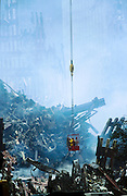 "22 SEPTEMBER 2011 - NEW YORK, NY: With smoke still rising from the rubble, recovery workers work from a bucket hanging from a crane  lift to survey the wreckage of the World Trade Center complex at ""Ground Zero"" of the WTC terrorist attack, Sept. 22, 2001, eleven days after the attack.  More than 2,900 people were killed when terrorists crashed two airliners into the towers on Sept. 11, 2001.   PHOTO BY JACK KURTZ"
