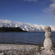 A snow man on the edge of Lake Wakatipu in Queenstown with the snow covered Remarkables mountain range providing a stunning backdrop after winter snowfalls..Queenstown is nestled on the shores of the crystal clear waters of Lake Wakatipu in the Central Otago region of the South Island of New Zealand..Queenstown is New Zealand's premier tourist destination providing an abundance of year round outdoor activities for both young and old. Queenstown, Central Otago, South Island, New Zealand. 10th July 2011. Photo Tim Clayton..