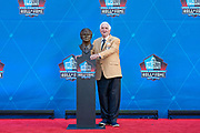 Aug 3, 2019; Canton, OH, USA; Gil Brandt poses with bust during the Pro Football Hall of Fame Enshrinement at Tom Benson Hall of Fame Stadium. (Robin Alam/Image of Sport)
