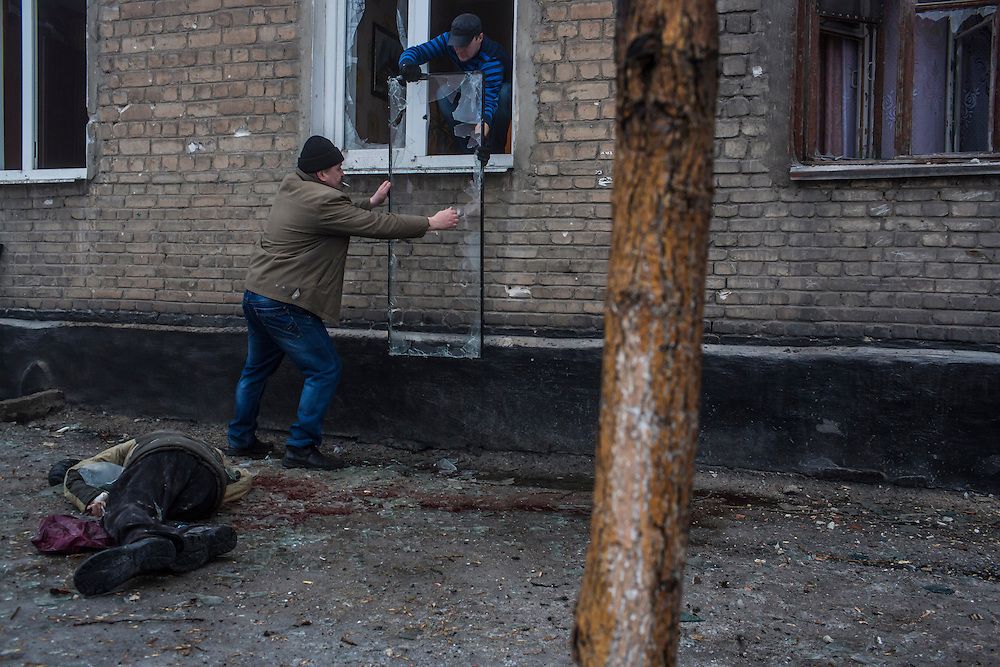 DONETSK, UKRAINE - JANUARY 30, 2015: The body of a man lies on the sidewalk as other men remove a broken window pane from its frame in Donetsk, Ukraine. A rocket or mortar struck the road, breaking the windows and killing at least two men on the sidewalk. At least five people were killed in a separate attack nearby when a rocket struck the parking lot outside a center for the distribution of humanitarian aid. CREDIT: Brendan Hoffman for The New York Times
