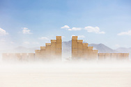The Temple of Direction in the dust<br /> by: Geordie Van Der Bosch<br /> from: San Francisco, CA<br /> year: 2019<br /> <br /> The Temple of Direction is organized linearly. It recreates a restricted passage which expands in the center into a large hall. This is a response to the openness of the playa; it creates a space traveled end to end; versus wandering an open plan; this temple provides direction and focus. Linearity also reflects the passage of life; all lives have a beginning, a middle and an end which metaphorically is included in this temple's form. Following this metaphor a variety of spaces are created; narrow spaces and wide spaces, dark spaces and bright spaces. Tunnels create intimate experiences with shade.. A large central hall expands in width and height providing a bright area suitable for gatherings.<br /> <br /> URL: https://www.templeofdirection.org<br /> Contact: templeofdirection@gmail.com<br /> <br /> https://burningman.org/event/brc/2019-art-installations/?yyyy=&artType=H#a2I0V00000167U9UAI