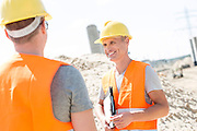 Happy supervisor discussing with colleague at construction site