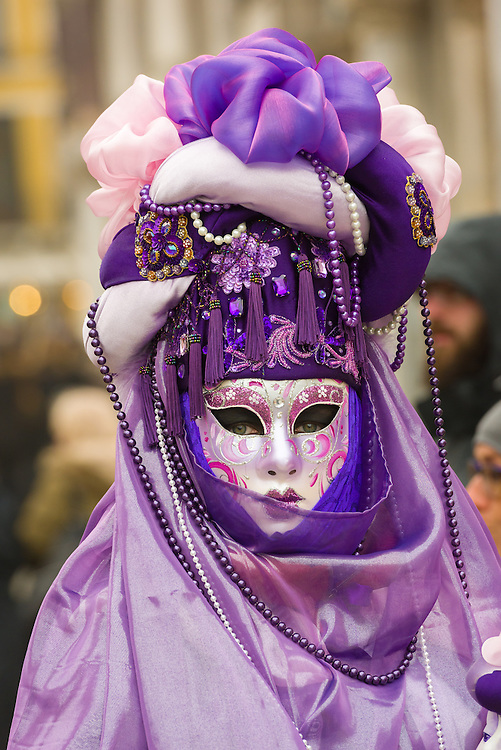 A woman is seen in St Mark's Square wearing a traditional Volto mask during the 2017 Venice Carnival