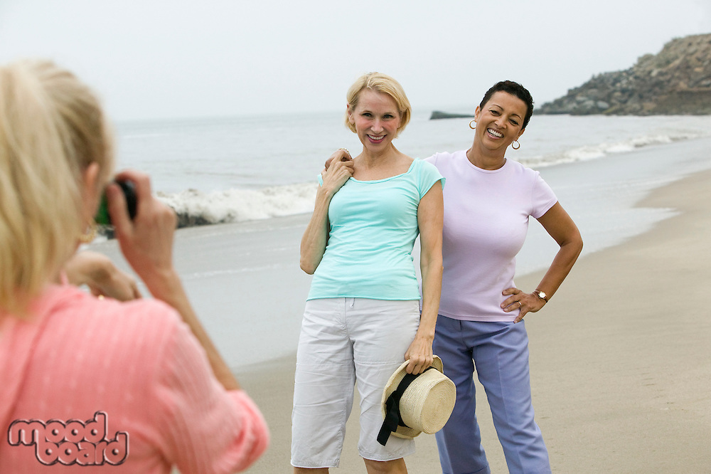 Two women being photographed on beach