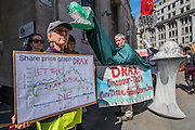 A puppet Draxosaurus symbolises their view that Drax should be extinct technology or at least shoul be axed - #AxeDrax protest outside the annual Drax shareholder AGM. Protestors demanded cleaner, greener energy generation systems. They continued on to the Department of Energy and Climate Change to deliver a petition demanding that subsidies given to Drax, for burning biomass, be stopped for making climate change worse.